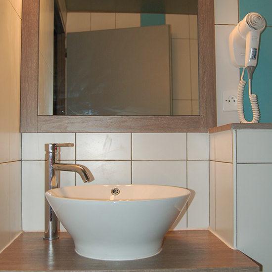 Salle d'eau avec vasque simple et sèche-cheveux
