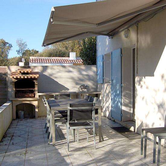 Terrasse ensoleillée avec barbecue et salon de jardin