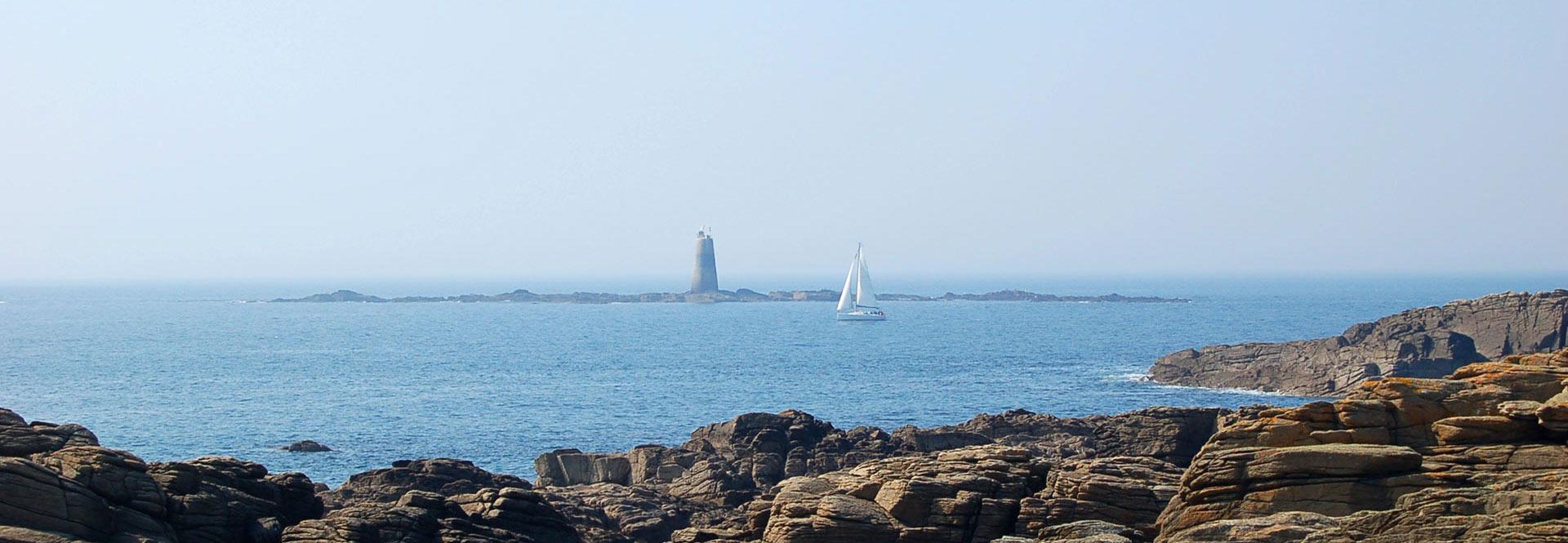 Vue sur a phare depuis la côte rocheuse vendéenne